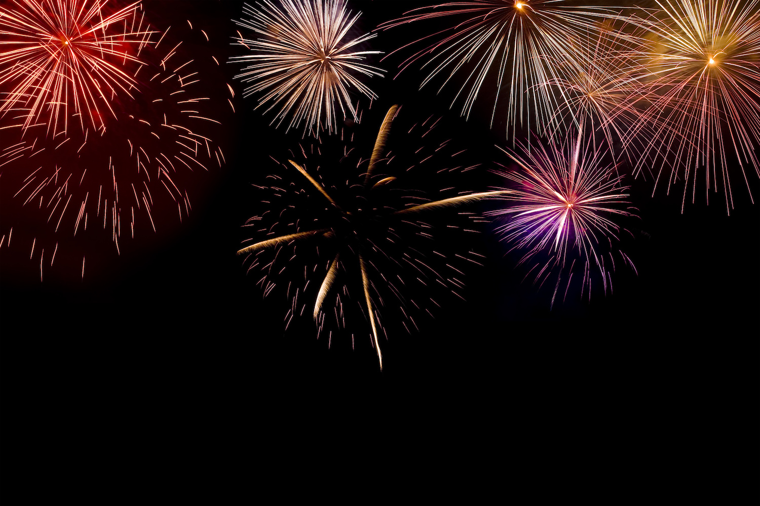 Multiple brightly coloured fireworks display exploding